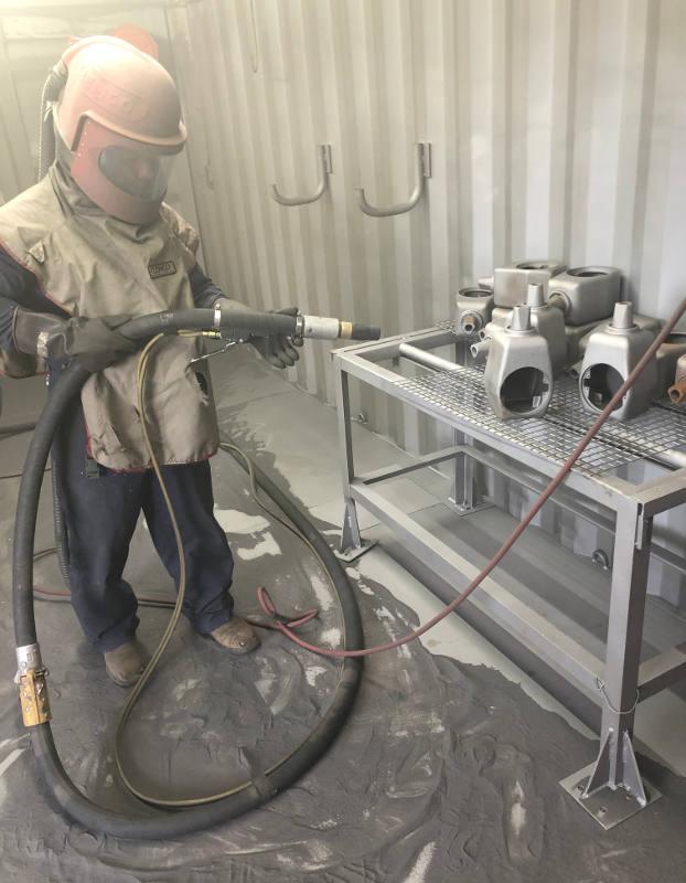 employee sandblasting metal